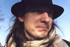 Photo affiche Unique au monde : Noé Cendrier, chapeauté, imberbe, 3/4 face, moue dubitative/amusée