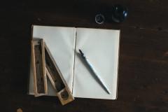Plume et plumier sur un livre vierge surmonté d'un encrier par Kira auf der heide sur Unsplash.com
