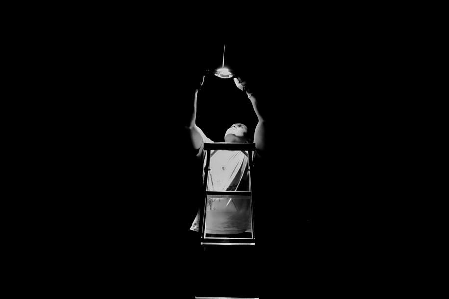 Homme sur une échelle réglant une lampe au milieu de l'obscurité par Youssef al Nasser sur Unsplash.com