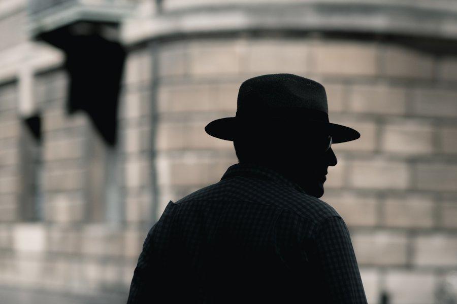 buste d'homme avec un fedora et des lunettes, de 3/4 dos et à contre-jour dans la rue, par Craig Whitehead sur Unsplash.com